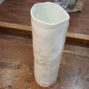 Tube vase with floral imprint made of porcelain.