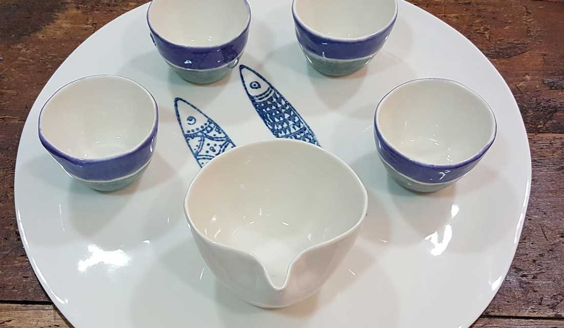 Round porcelain tray with cups and milk jug